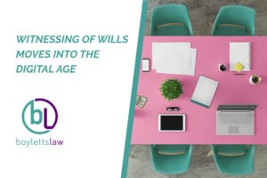 Image of a tablet and a laptop on pink meeting room table for blog about witnessing of wills moves into the digital age